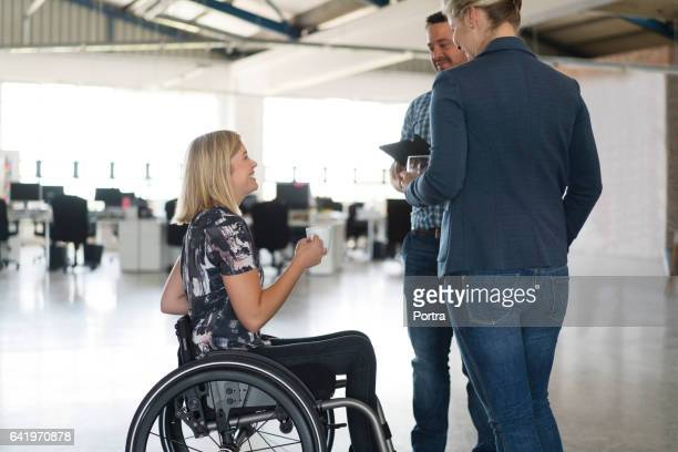 Disabled businesswoman discussing with colleagues