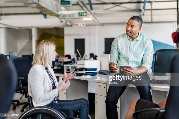 Disabled businesswoman sharing ideas with coworker