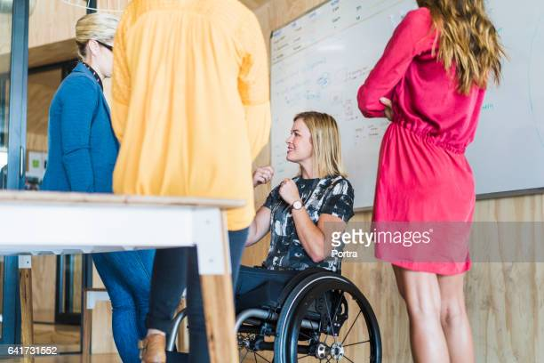 Disabled businesswoman with colleagues in office