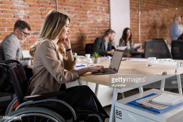 disabled businesswoman working on laptop in the office. - incidental people stock pictures, royalty-free photos & images