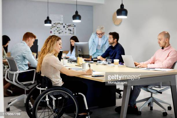 disabled businesswoman working with colleagues in office - differing abilities fotografías e imágenes de stock
