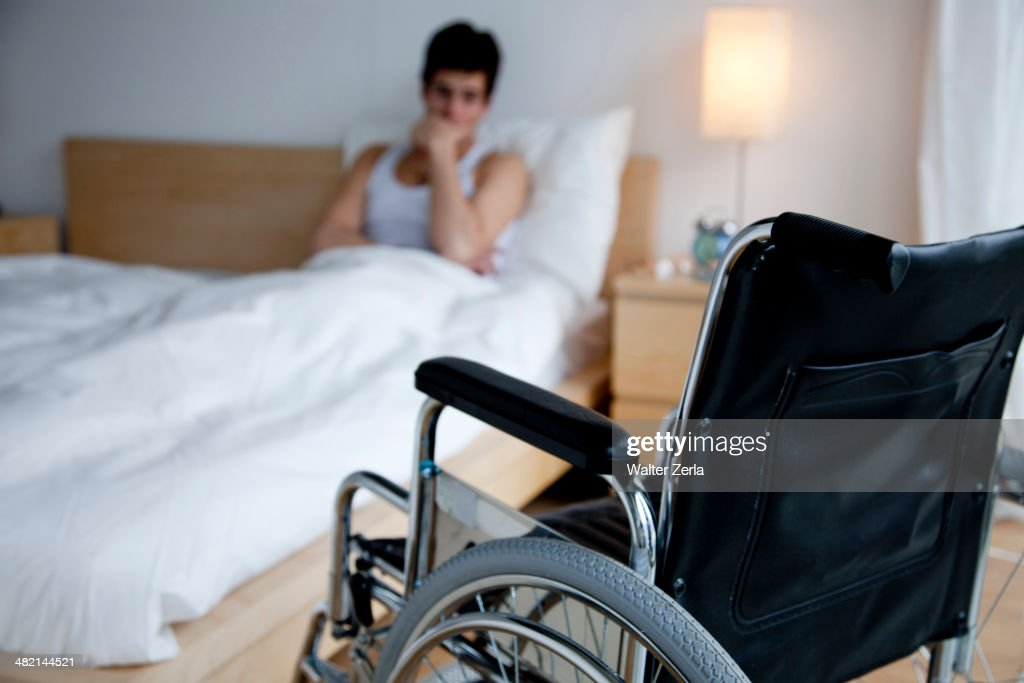 Disabled Caucasian man in bed out of reach of wheelchair : Foto de stock