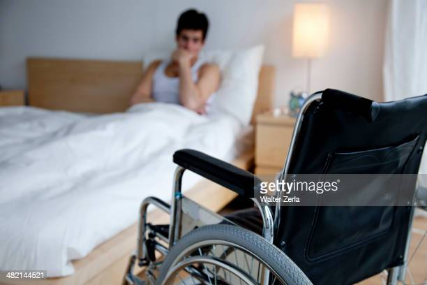 disabled caucasian man in bed out of reach of wheelchair - paraplegic stock photos and pictures