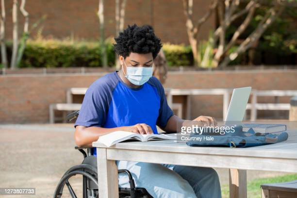 disabled college student sitting at outdoor desk - wheelchair stock pictures, royalty-free photos & images