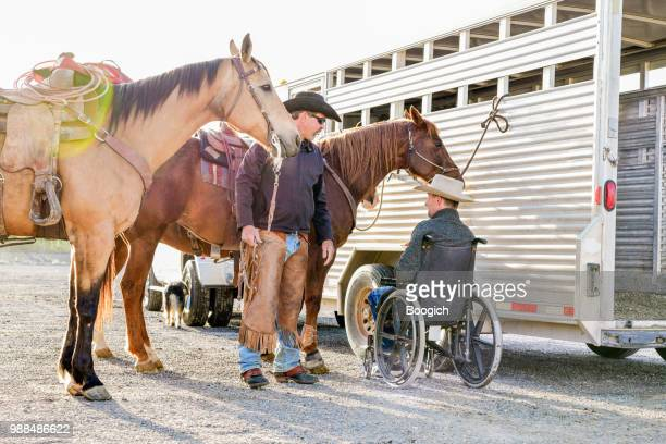 disabled cowboy in wheelchair with horses talking with friend outside rodeo event - spanish fork utah stock pictures, royalty-free photos & images