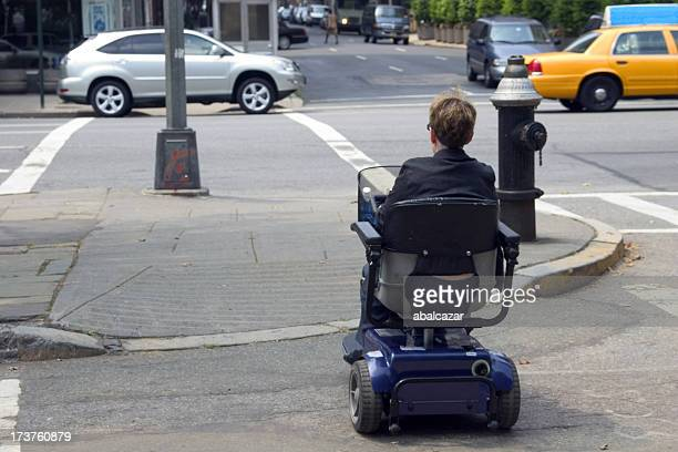 disabled crossing the street - mobility scooter stock photos and pictures