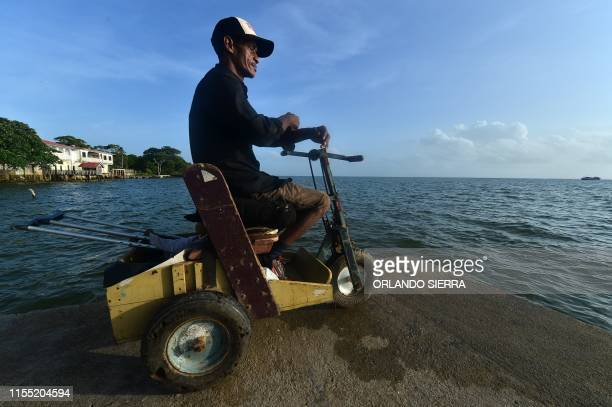 Disabled diver Ernesto McLean rides a makeshift handicapped cart as he watches the sea in Puerto Lempira Honduras on July 8 2019 Thousands of fishing...