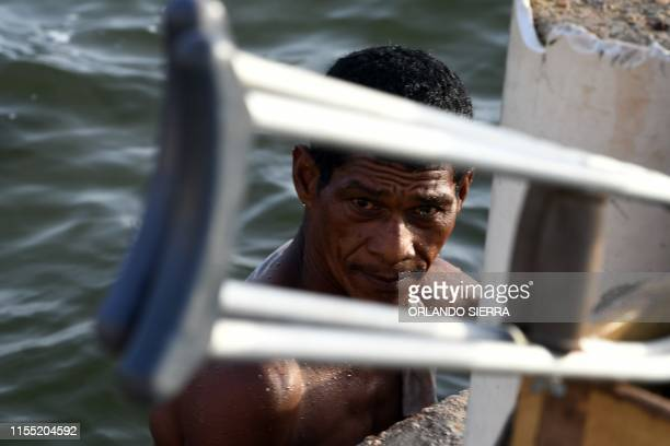Disabled diver Ernesto McLean takes a bath in the sea as he looks at the camera in Puerto Lempira Honduras on July 8 2019 Thousands of fishing divers...