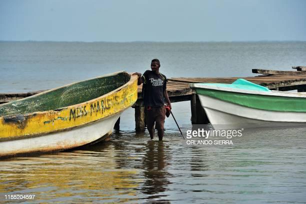Disabled diver Jaime Lemus Matute using a makeshift walking stick stands between boates in Prumnitara Puerto Lempira Honduras on July 8 2019...