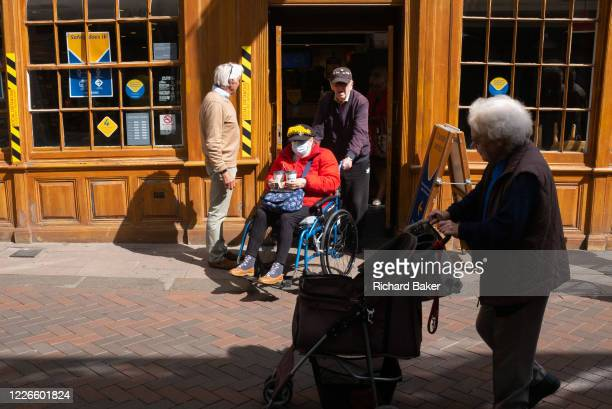 Disabled elderly lady in a wheelchair is pushed from a branch of Greggs during the Coronavirus pandemic, on 11th July 2020, in Bury St. Edmunds,...