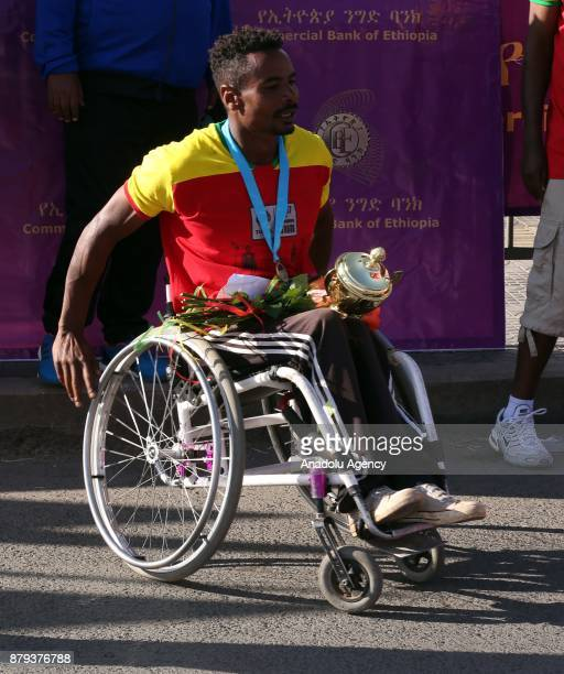 Disabled Ethiopian athlete Demesew Abera carries flowers and his award after finishing first in the men's Great Ethiopian Run at Adwa Square in Addis...