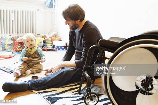 disabled father with son playing on floor - sigrid gombert stock pictures, royalty-free photos & images
