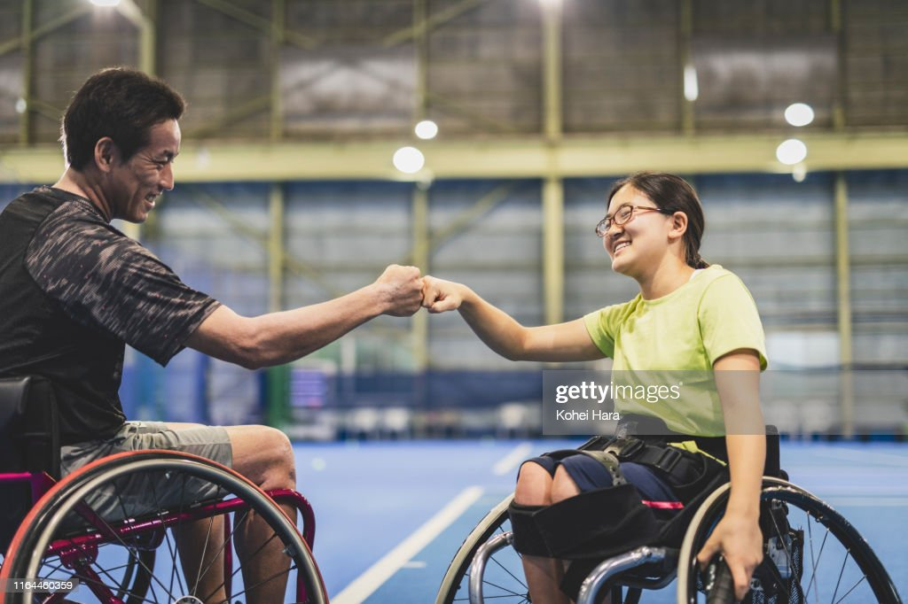 Disabled female athlete doing a fist bump with her coach during playing wheel chair tennis : ストックフォト