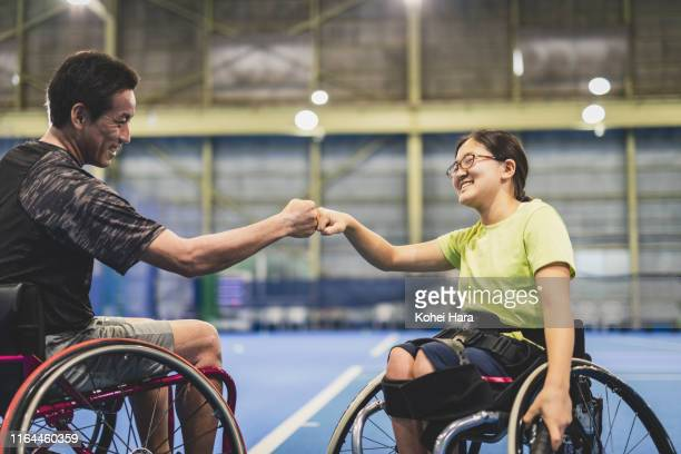 disabled female athlete doing a fist bump with her coach during playing wheel chair tennis - differing abilities fotografías e imágenes de stock