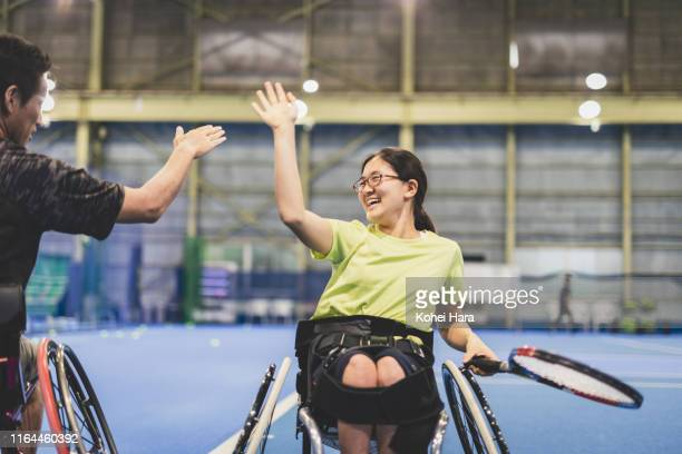 disabled female athlete doing a high five with her coach during playing wheel chair tennis - disabilitycollection stock-fotos und bilder