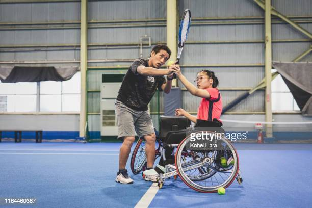 disabled female athlete practicing wheel chair tennis with her coach - 車いすテニス ストックフォトと画像