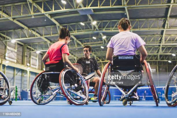 disabled female athletes of wheel chair tennis training with their coach - 車いすテニス ストックフォトと画像