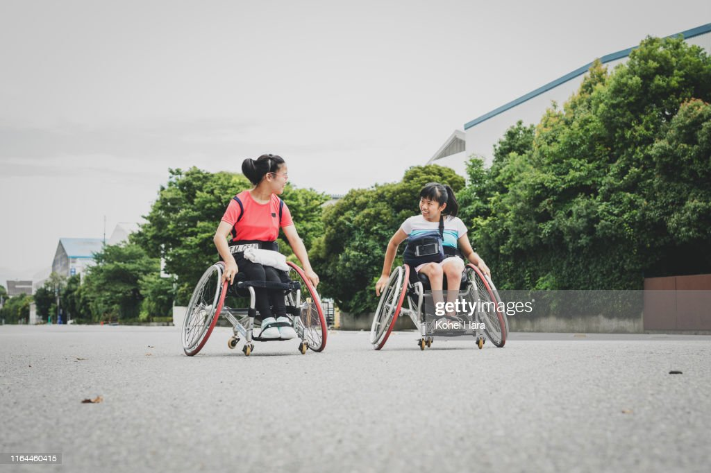 Disabled female athletes on wheel chair for wheel chair tennis walking together on the road : ストックフォト