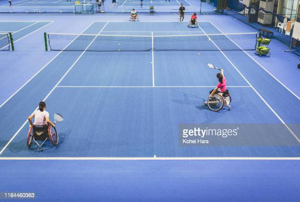 Disabled female athletes playing wheel chair tennis with their coach