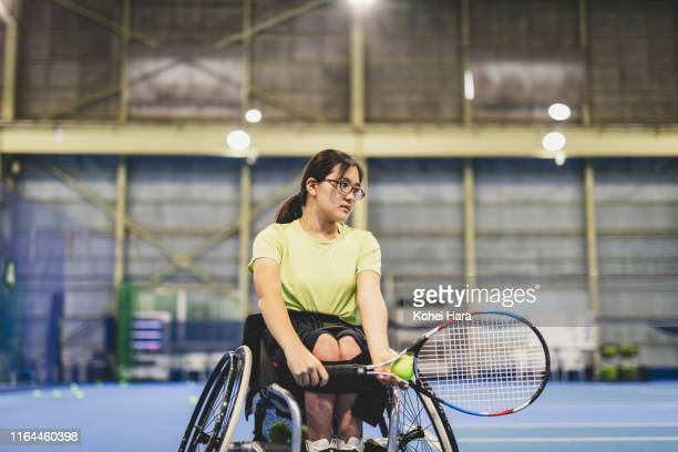 disabled female athletes serving during playing wheel chair tennis - 車いすテニス ストックフォトと画像
