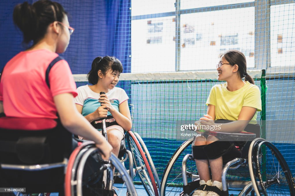 Disabled female athletes talking while playing wheel chair tennis : Stock Photo