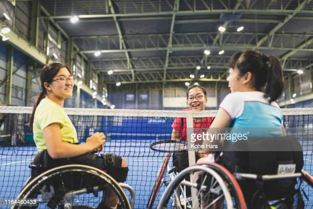 Disabled female athletes talking while playing wheel chair tennis