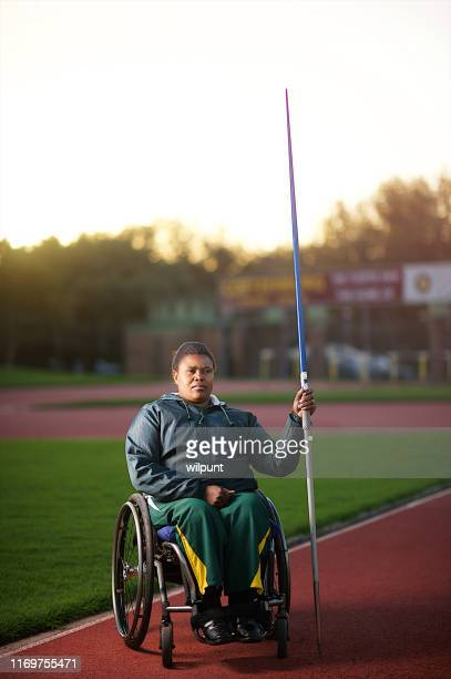 disabled female javelin thrower in wheelchair in stadium - athleticism stock pictures, royalty-free photos & images