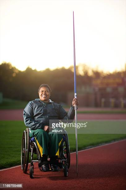 Disabled female javelin thrower in wheelchair in stadium smiling
