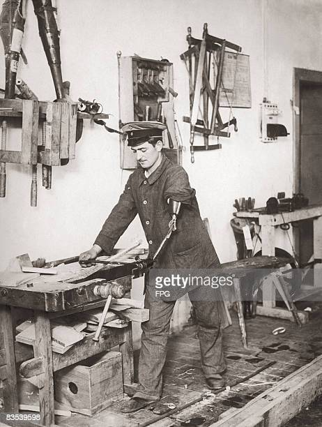 A disabled German exserviceman working as a carpenter with the aid of a prosthetic arm Germany circa 1919