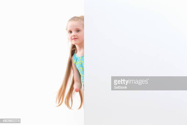 Disabled Girl In Swimsuit Looks Around White Wall At Studio