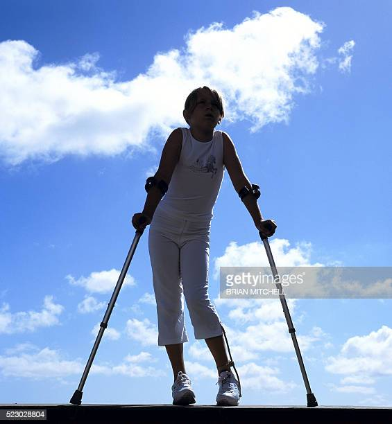 disabled girl with leg brace aged 11 years using elbow crutches - polio virus stock pictures, royalty-free photos & images