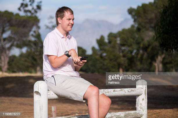 disabled golfer using mobile phone to keep track of score - of deformed people stock pictures, royalty-free photos & images