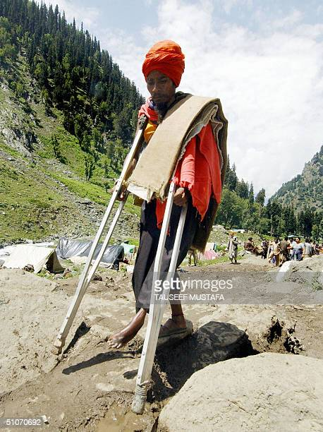 A disabled Indian Hindu pilgrim walks with the aid of crutches close to the village of Chandanwari some 114kms south of Srinagar15 July 2004 Some...