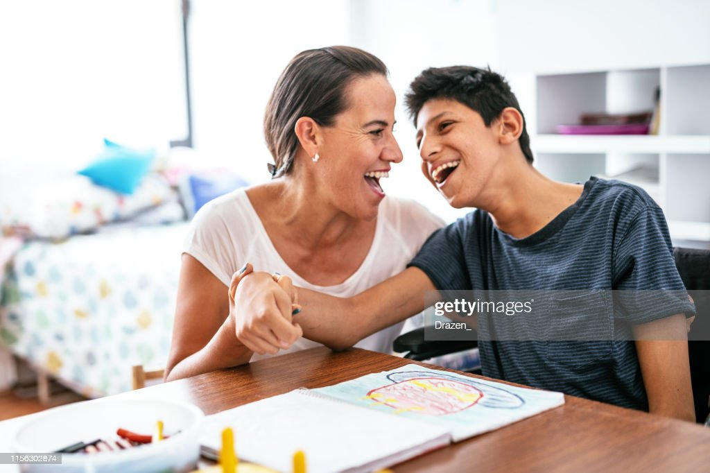 Disabled Latino teenager with Celebral Palsy and mother laughing. : Stock Photo