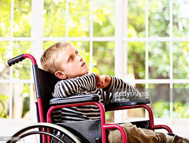 Disabled little boy in wheelchair looks up wistfully