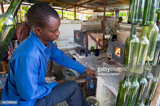 Disabled local man blowing glass using recycled materials for the wholesale and retail consumer market at the Shanga House in Arusha Tanzania