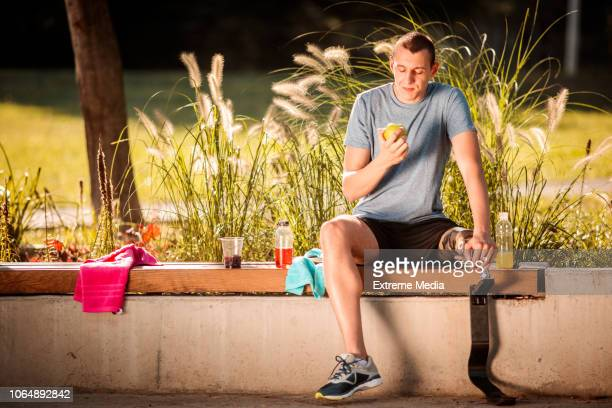 Disabled male athlete with prosthetic leg sitting on the park bench