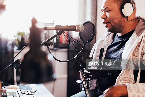 Disabled male singer recording music in studio