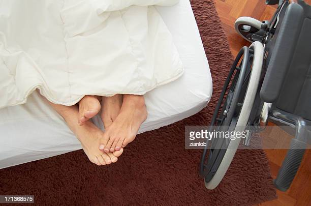 Disabled man having sex in bed with his partner.