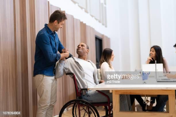 homem com deficiência ajudando pelo colega de trabalho no local de trabalho - acessibilidade - fotografias e filmes do acervo