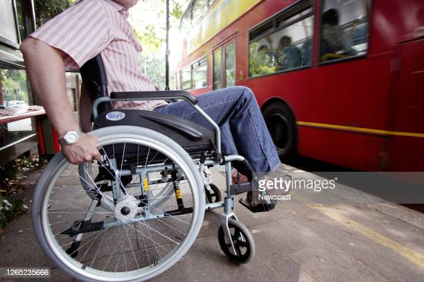 Disabled man in a wheelchair at a bus stop in London, England.