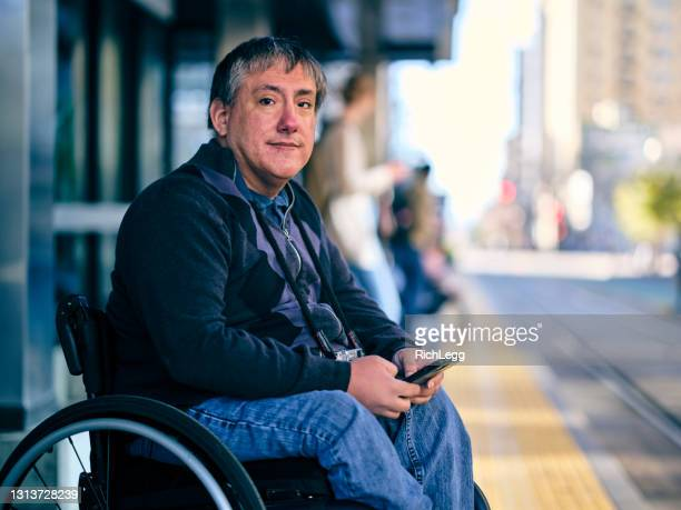 disabled man in a wheelchair waiting at a train station - physical disability stock pictures, royalty-free photos & images