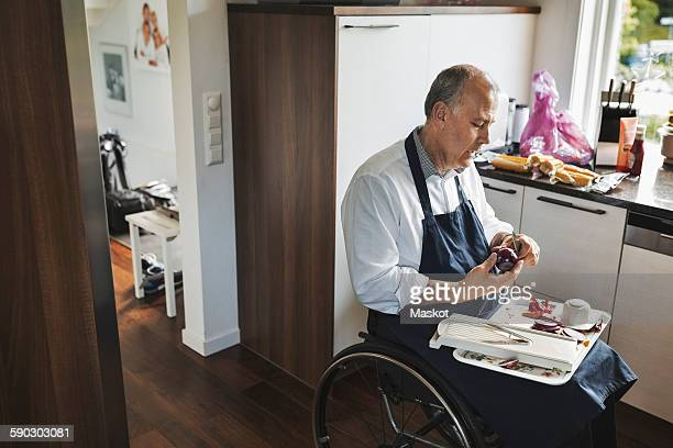 disabled man in wheelchair cutting onion at kitchen - one mature man only stock pictures, royalty-free photos & images