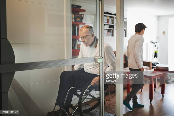 Disabled man in wheelchair exiting lift at home