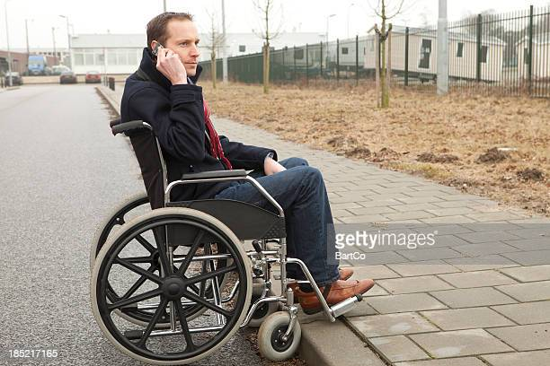 disabled man in wheelchair looking at pavement and calling help - flaccid stock photos and pictures