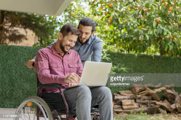disabled man in wheelchair using laptop at backyard - persons with disabilities stock pictures, royalty-free photos & images