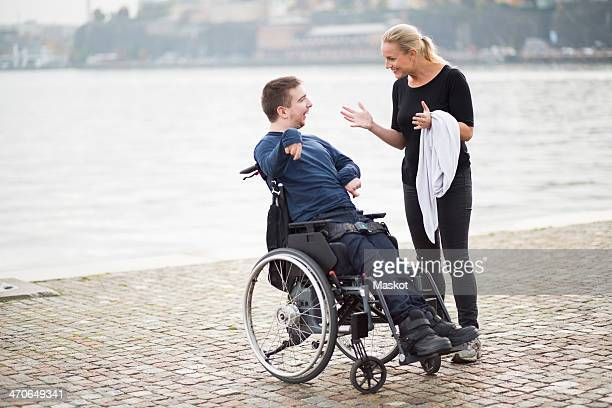 Disabled man on wheelchair taking with female caretaker by lake