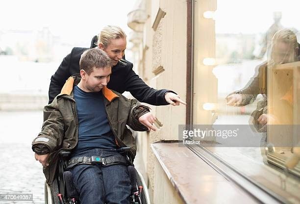 Disabled man on wheelchair widow shopping with caretaker