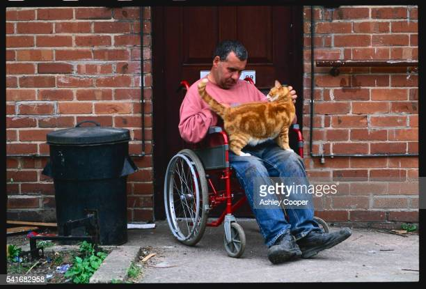 Disabled Man Petting a Ginger Cat