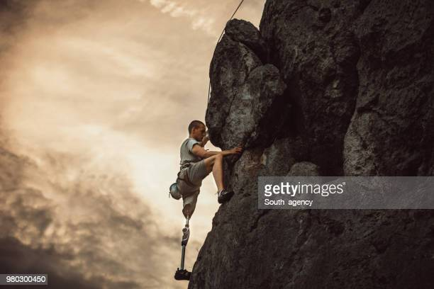 disabled man rock climbing - physical disability stock pictures, royalty-free photos & images